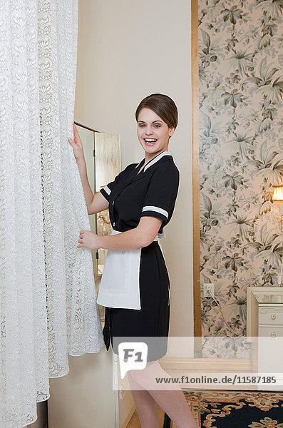 Zimmermädchen beim Einstellen des Vorhangs  lachend