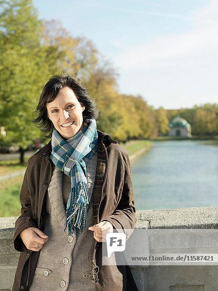 Frau steht im Herbst auf Flussbrücke