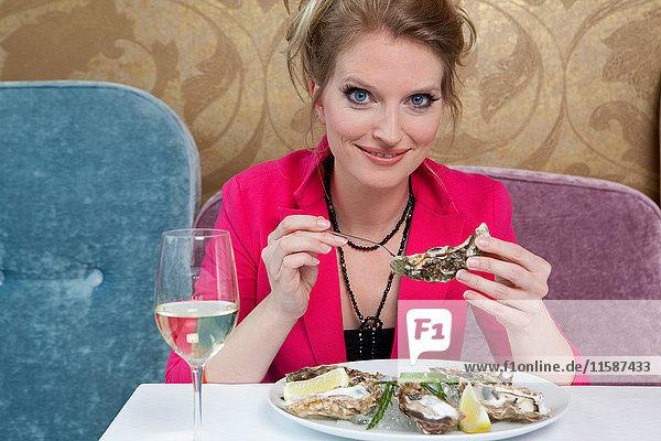 Frau mit Austern im Restaurant
