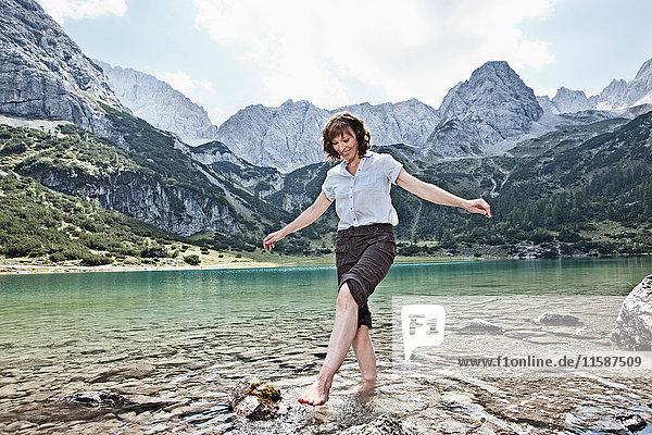 Frau mit nackten Füßen spielt im See