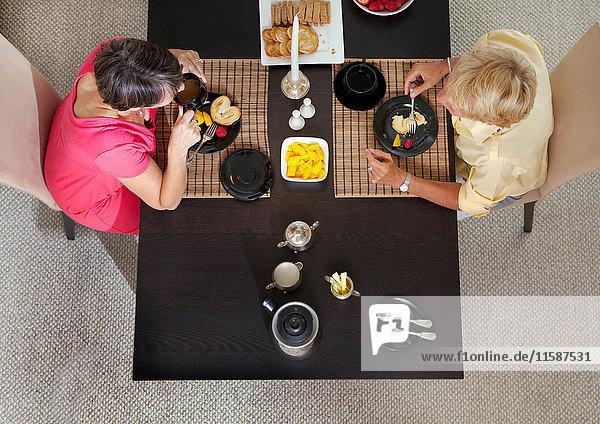 Reife lesbische Paare beim Essen am Tisch  Blick über den Kopf