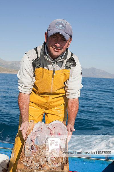 Fischer auf dem Boot  der den Fisch präsentiert