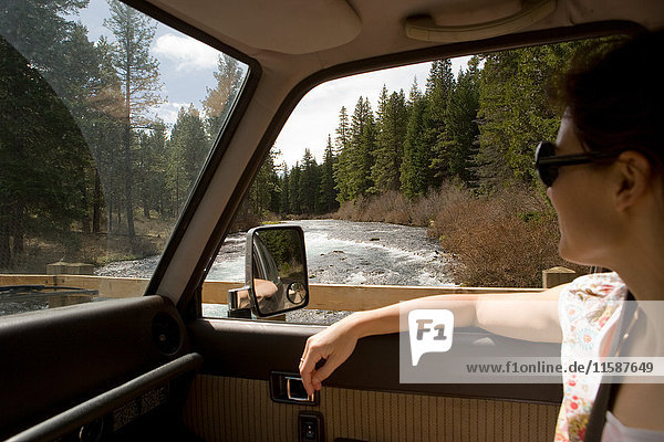 Woman looking through car window at forest scenery