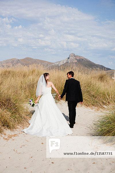 Braut und Bräutigam beim Strandspaziergang