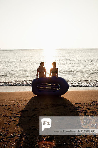 Women with inflatable boat on beach