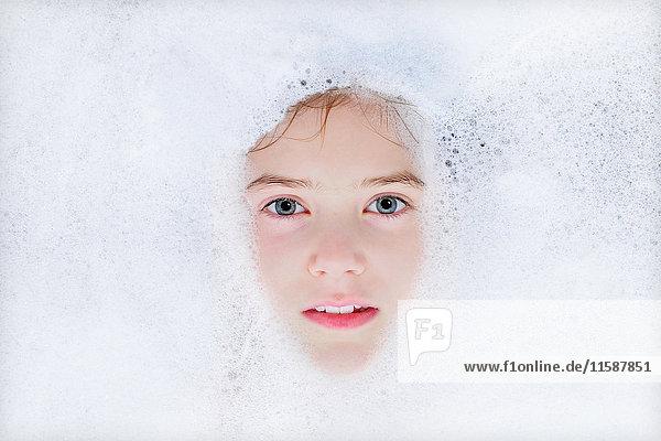 Nahaufnahme eines im Schaumbad schwimmenden Mädchens Nahaufnahme eines im Schaumbad schwimmenden Mädchens