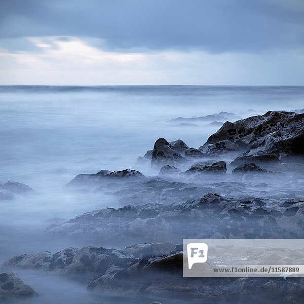 Felsige Küste in der Abenddämmerung