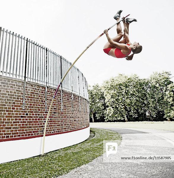 Athlet springt über Ziegelmauer