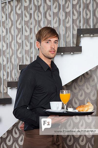 Kellner hält Frühstückstablett im Café