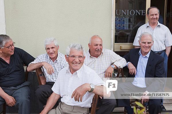 sechs alte Männer sitzen draußen und lachen