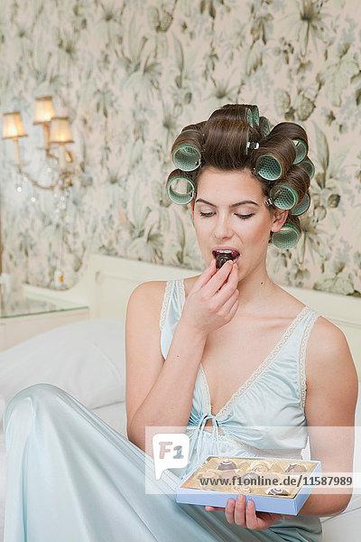 Frau isst Schokolade aus einer Pralinenschachtel