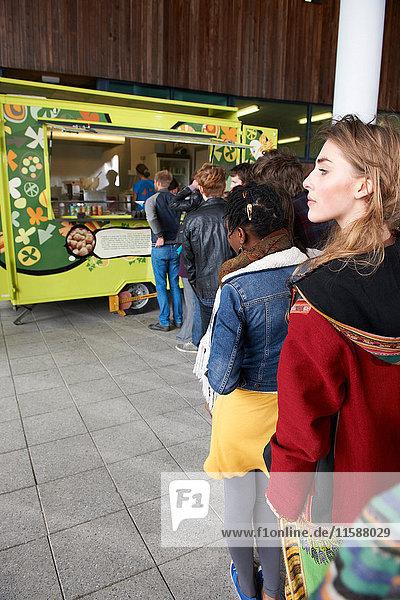 Menschen stehen Schlange für Lebensmittelwagen