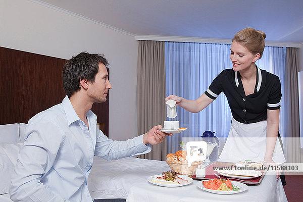 Zimmermädchen bedient Geschäftsmann in seinem Zimmer
