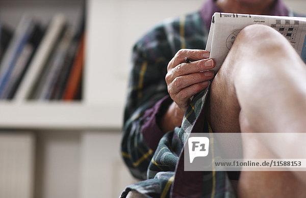 Älterer Mann im Bademantel entspannt mit Zeitung