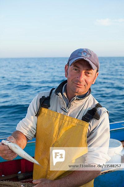 Fischer auf seinem Boot  lachend