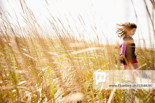 Girl running through long grass