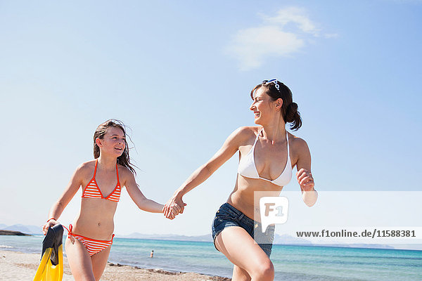 Mutter mit Tochter läuft am Strand entlang