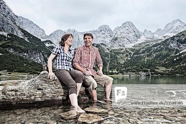 Lächelndes Paar mit baumelnden Füßen im See