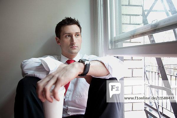 Am Fenster sitzender Geschäftsmann mit Einwegbecher