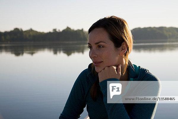 Woman thinking next to lake