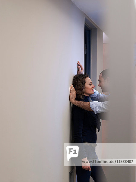 Couple kissing in an office corridor