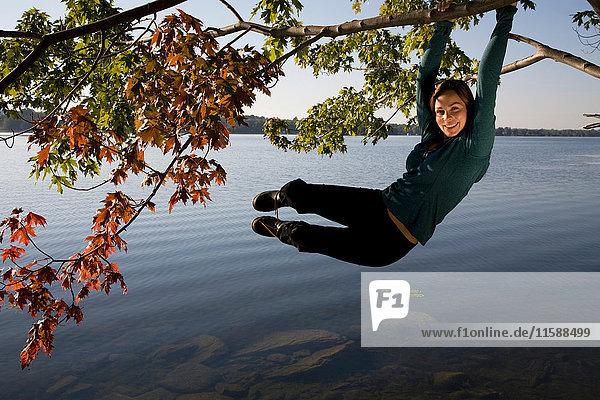 Woman swinging from tree