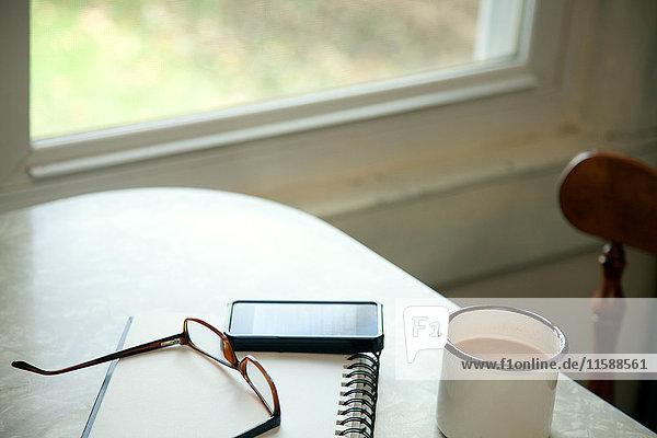 Tisch mit Kaffeetasse und Brille