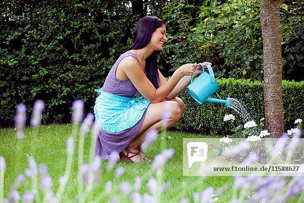 Frau bewässert Pflanzen im Hinterhof