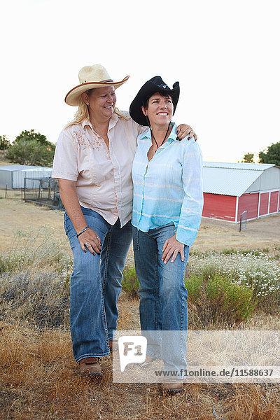 Reifes lesbisches Paar steht zusammen auf der Ranch und lächelt