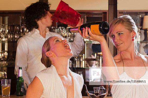 zwei Mädchen plus Barkeeper  die Spaß haben