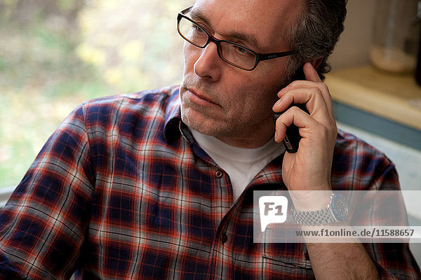 Mature man using cellphone at home