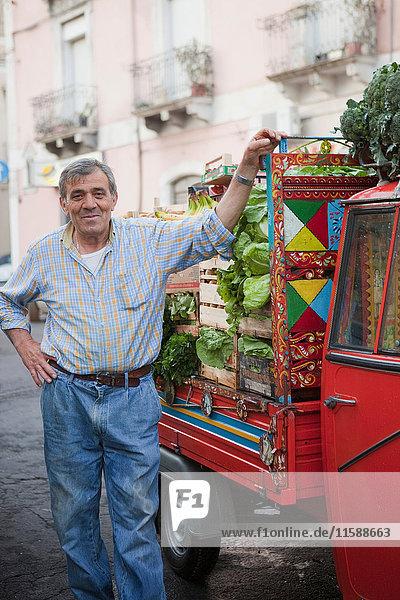 Obstverkäufer neben seinem Affen-Transporter
