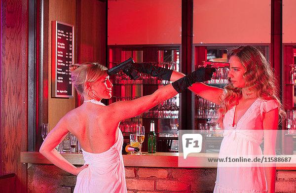 zwei Mädchen an der Bar mit Plastikwaffen