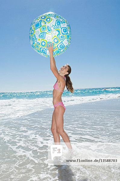Ein Mädchen spielt mit einem Strandball