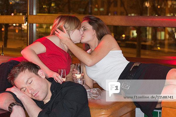 zwei Frauen küssen sich  im Vordergrund ein schlafender Junge