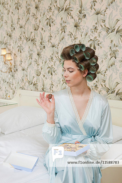 Frau im Bett mit Pralinenschachtel
