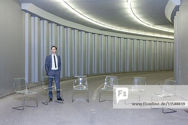 Geschäftsmann durch Stühle im leeren Flur