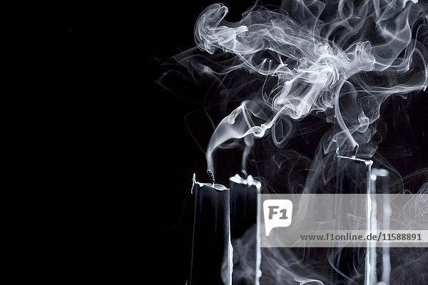 Nahaufnahme von rauchenden schwarzen Kerzen