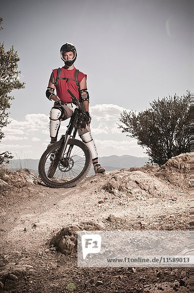 Mountain biker standing on rocky path
