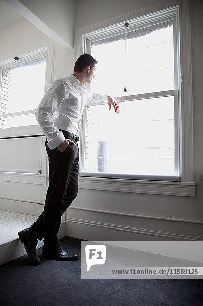 Geschäftsmann  der aus dem Fenster schaut