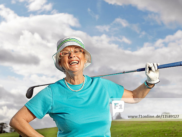 Reife Dame beim Golfspielen