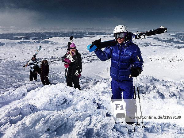 4 Personen  die auf dem Gipfel des Berges posieren.