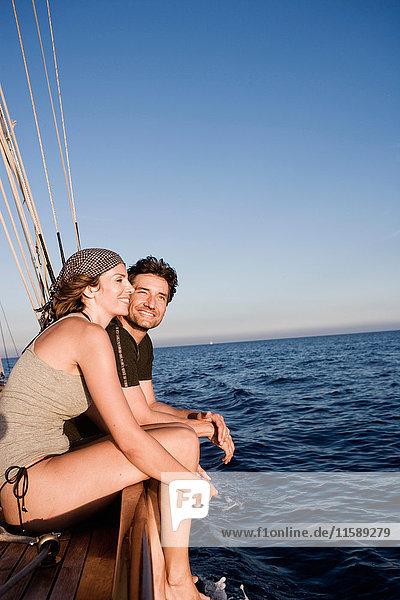 Paar  das auf der Reling eines Bootes sitzt