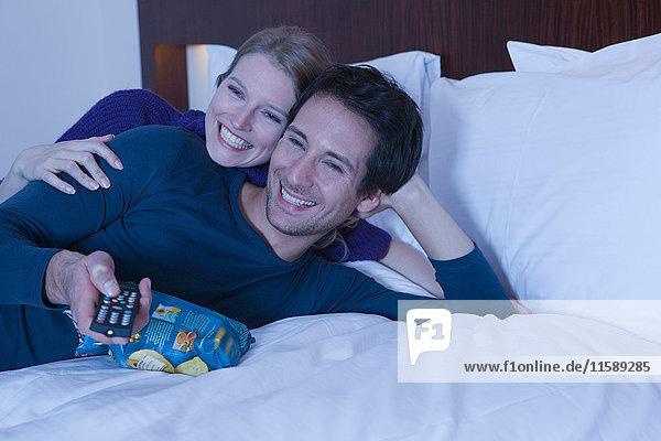 Paar im Bett  das fernsieht und lacht