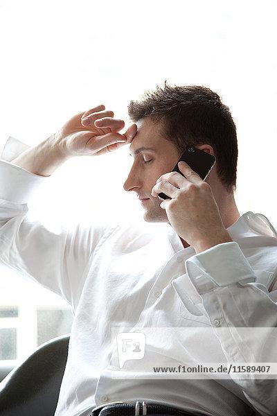Geschäftsmann am Smartphone mit geschlossenen Augen