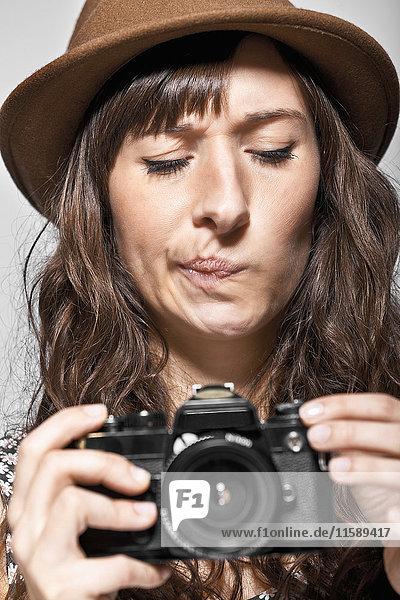 Confused woman examining camera