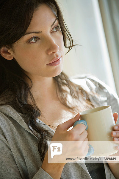 Junge Frau trinkt Kaffee am Fenster
