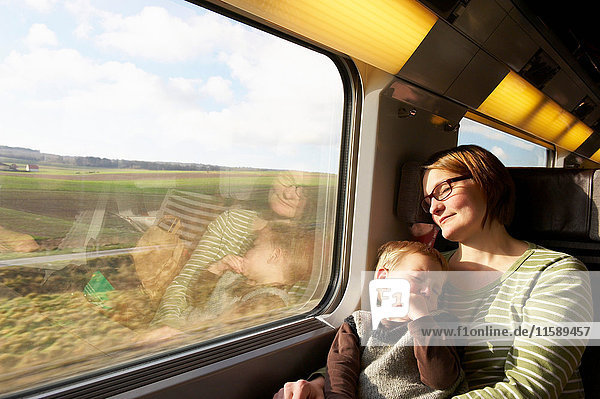 Mother and son asleep on train