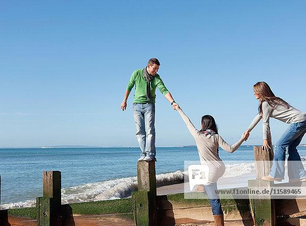 People helping friend onto jetty