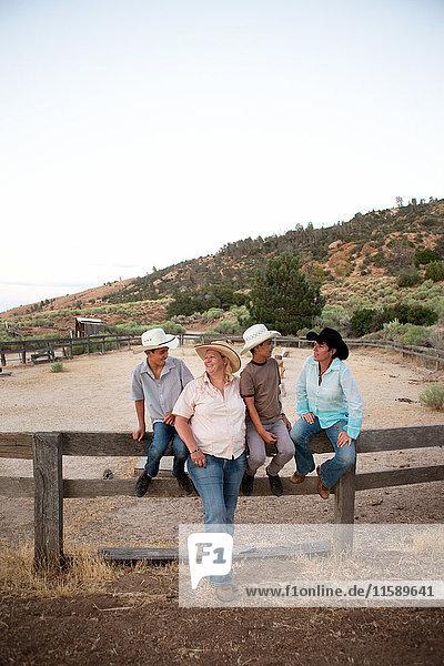 Familie sitzt zusammen auf der Ranch